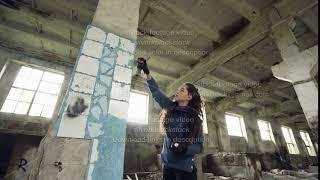Attractive girl urban artist is painting graffiti in abandoned building with dirty walls and windows